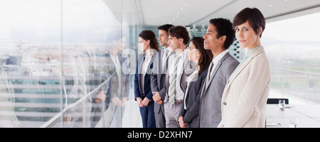 Business people in conference room looking out window - Stock Photo