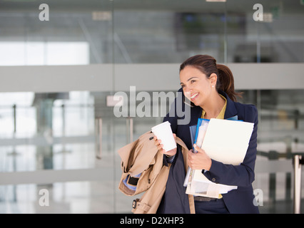 Smiling businesswoman multitasking on cell phone with coffee and paperwork - Stock Photo