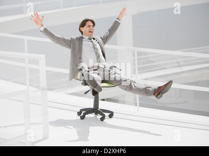 Carefree businessman sliding down walkway on office chair with wheels - Stock Photo