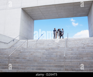 Business people meeting at top of urban stairs - Stock Photo