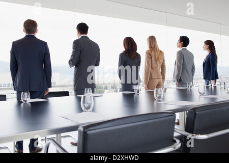 Business people in a row looking out conference room window - Stock Photo