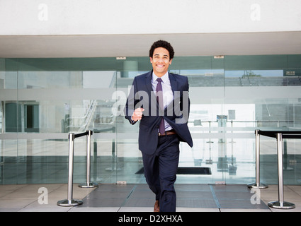 Portrait of smiling businessman running in front of airport - Stock Photo