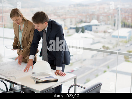 Architects reviewing blueprints in office overlooking city - Stock Photo
