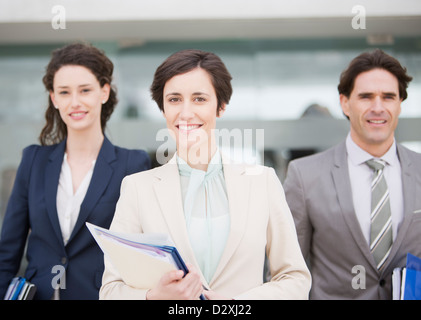 Portrait of smiling business people holding files - Stock Photo