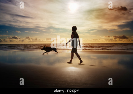 Silhouette of woman and dog walking on beach - Stock Photo