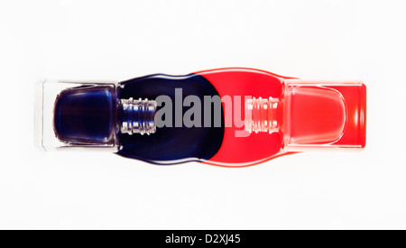 Blue and coral fingernail polish spilling from bottles - Stock Photo