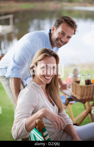 Portrait of smiling couple enjoying picnic at lakeside - Stock Photo
