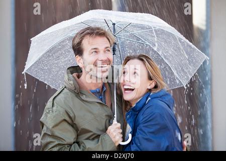 Happy couple under umbrella in downpour - Stock Photo