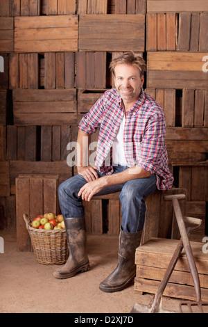 Portrait of smiling man sitting next to bushel of apples - Stock Photo