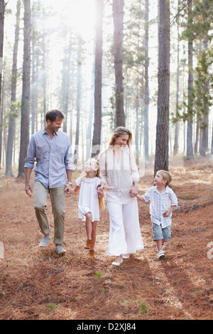 Happy family holding hands and walking in sunny woods - Stock Photo