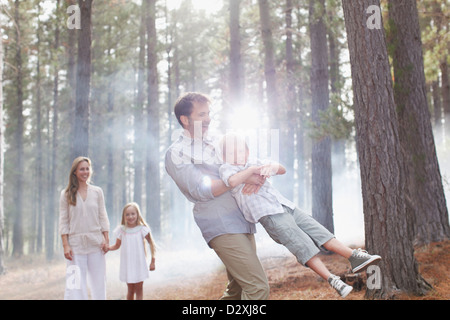 Happy family playing in sunny woods - Stock Photo