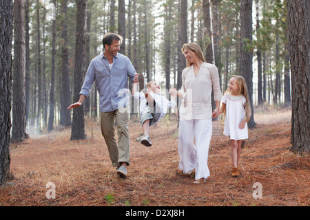 Happy family holding hands and walking in woods - Stock Photo