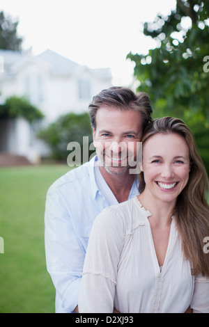 Portrait of smiling couple in yard with house in background - Stock Photo