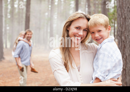 Portrait of smiling mother holding son in woods - Stock Photo