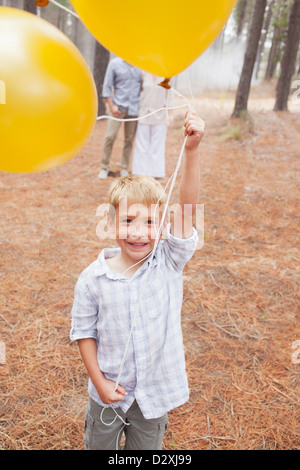 Portrait of smiling boy holding balloons in woods with parents in background - Stock Photo