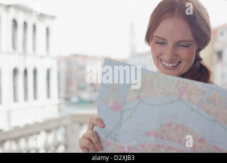Smiling woman looking down at map - Stock Photo