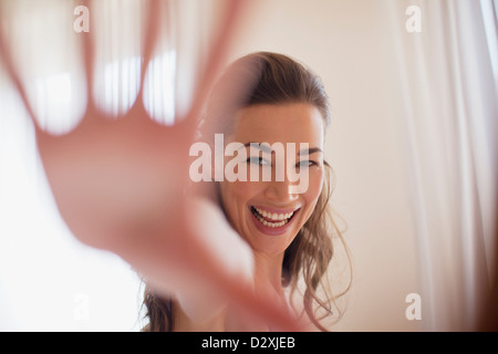 Portrait of smiling woman with hand outstretched - Stock Photo