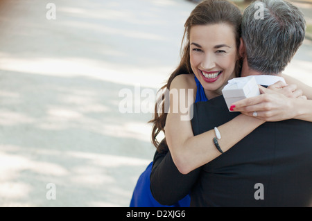 Portrait of smiling woman receiving gift from man - Stock Photo