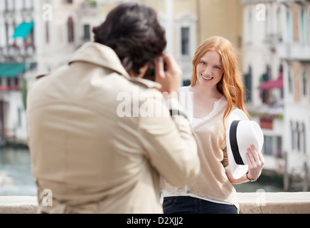 Man photographing smiling woman holding hat in Venice - Stock Photo