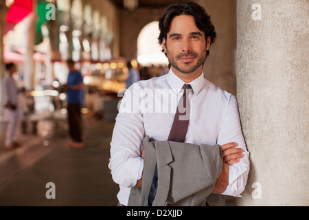 Portrait of smiling businessman leaning on pillar with arms crossed - Stock Photo