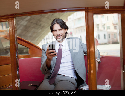 Portrait of smiling businessman with cell phone on boat in Venice - Stock Photo