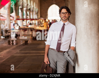 Portrait of confident businessman leaning against pillar at outdoor market - Stock Photo