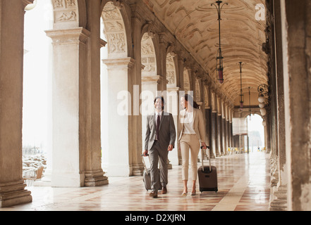 Smiling businessman and businesswoman pulling suitcases along corridor in Venice - Stock Photo