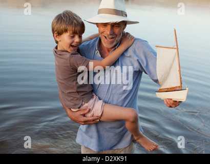 Smiling grandfather and grandson with toy sailboat wading in lake - Stock Photo