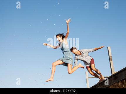 Exuberant couple jumping off dock - Stock Photo