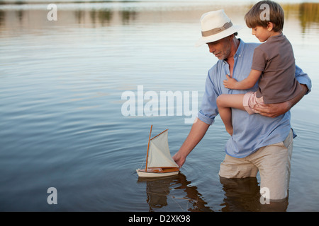 Grandfather and grandson wading in lake with toy sailboat - Stock Photo