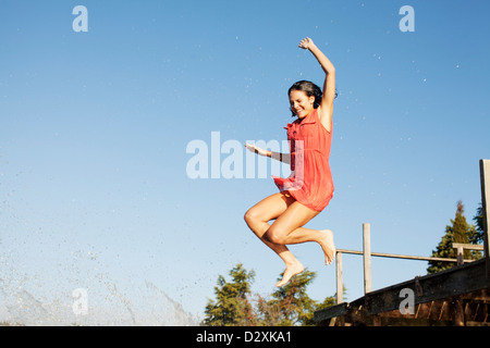 Smiling woman jumping off dock - Stock Photo