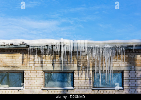 Very cold in winter concept. Huge icicles hanging on roof of a brick old rustic building on a background of frozen - Stock Photo