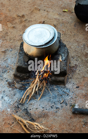 Boiling rice on an open fire in a rural indian village. Andhra Pradesh, India - Stock Photo