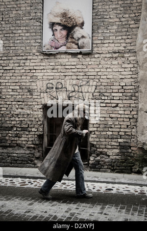 A man smoking in the street as he passes an advertising poster of an old woman. Vilnius Lithuania. - Stock Photo
