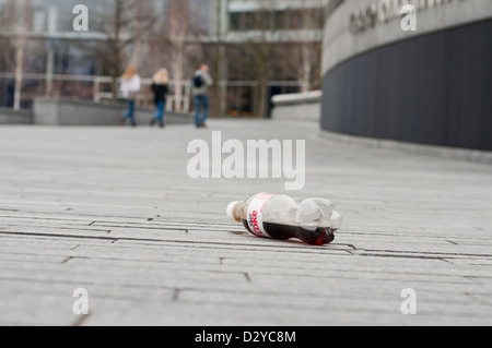 A half empty plastic diet coke bottle discarded as rubbish on the street with three people walking off in the background - Stock Photo