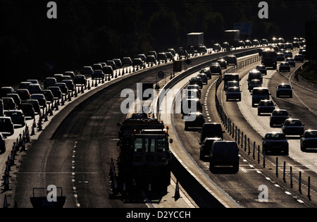 Cars queue and are delayed as traffic builds during maintenance on the M3, a UK motorway - Stock Photo