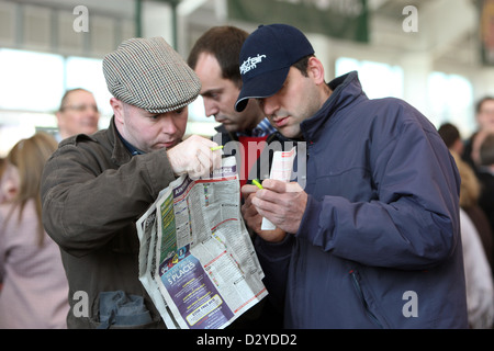 Liverpool, United Kingdom, Men on the racecourse study the racing paper - Stock Photo