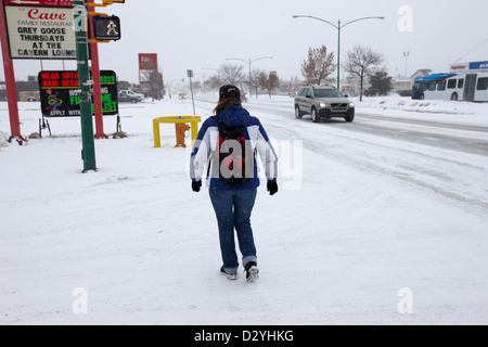 woman wearing backpack walking along 8th street in snowstorm Saskatoon Saskatchewan Canada - Stock Photo