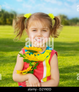 Picture of cute happy little girl wearing colorful dress and holding in hands beautiful sunflower bouquet, adorable - Stock Photo