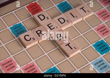 'Credit Debit' concept spelled out in Scrabble letters on Scrabble board - Stock Photo