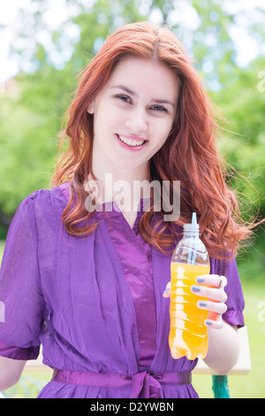 Portrait of a young woman in a park with a bottle of orange soda - Stock Photo