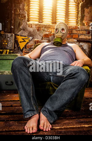person in a gas mask sits on an armchair - Stock Photo
