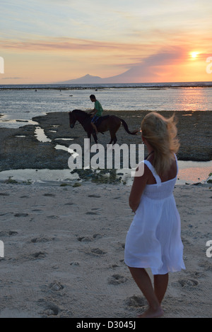 A woman with white dress watch an horseman and the sunset over Bali in Gili Trawangan; Lombok, Indonesia. - Stock Photo