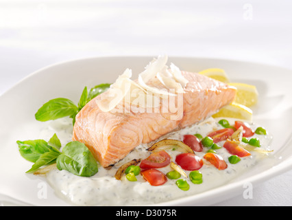 Dinner with delicious salmon in cream on a white plate - Stock Photo