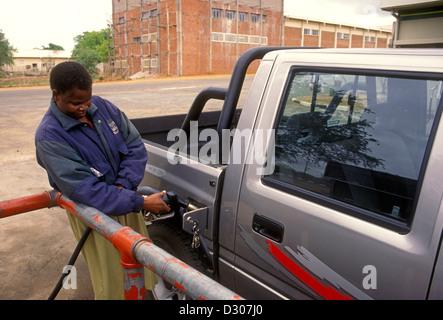 Zimbabwean man, adult man, gas station attendant, attendant, gas station, pumping gas, filling gas tank, Chiredzi, - Stock Photo