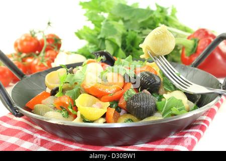 fresh Pasta pan with bell pepper, turnip greens, ham strips, tomatoes and garlic - Stock Photo