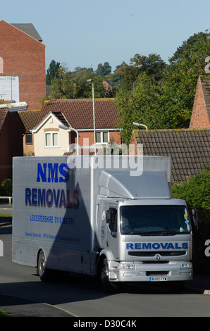 Removals lorry waiting outside a house on a housing estate in England. - Stock Photo