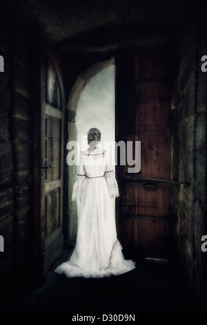 a woman in an elegant dress is standing in the gate of an old castle - Stock Photo