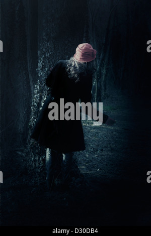a woman with a black coat is standing behind a tree - Stock Photo