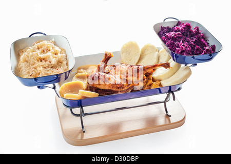 Roasted duck with dumplings, red and white cabbage on white background - Stock Photo